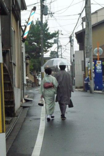 Un couple en habits tradictionnels se promenant sous la pluie dans les petites rues de Kyoto
